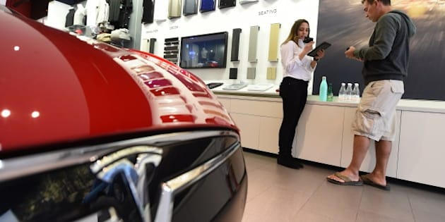 A salesrep (L) helps a customer pre-order the as yet unseen Tesla Model 3, in the Tesla store on the Third Street Promenade in Santa Monica, California, on March 31, 2016.   / AFP / ROBYN BECK        (Photo credit should read ROBYN BECK/AFP/Getty Images)