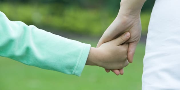 Mother and daughter holding hands, close-up of hands