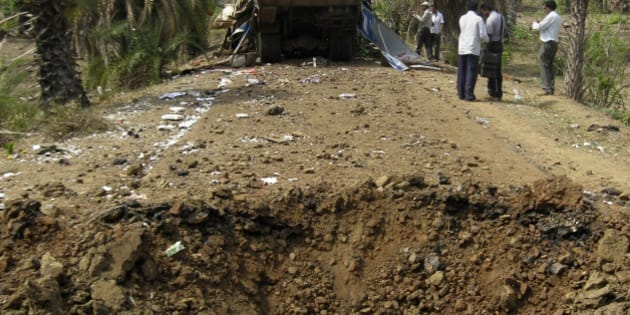 A crater is seen in foreground as officials inspect the wreckage of a bus in Dantewada district, about 350 miles (560 kilometers) south of Raipur, the capital of Chhattisgarh state, India, Tuesday, May 18, 2010. Indian Home Minister Palaniappan Chidambaram said Tuesday the government was prepared to enter into peace talks with Maoist rebels, but only if the insurgents halt all attacks for 72 hours. The offer followed a rebel ambush Monday on a packed bus in central India that killed 31 police officers and civilians. (AP Photo)