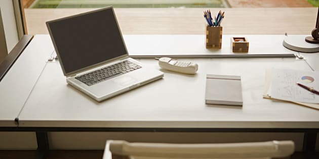 Desk with laptop, telephone and paperwork by window in home office