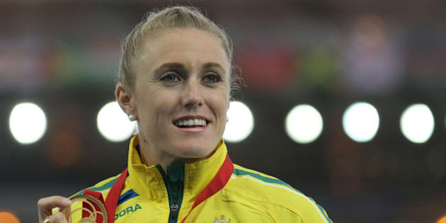 Sally Pearson of Australia winner of the women's 100 meter hurdle race poses for photographs on the podium following the medal ceremony for the event at Hampden Park Stadium during the Commonwealth Games 2014 in Glasgow, Scotland, Saturday Aug. 2, 2014. Pearson won the race Friday.(AP Photo/ Scott Heppell)