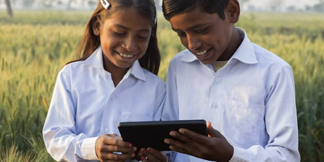 Indian brother and sister wearing school uniform looking at tablet device.
