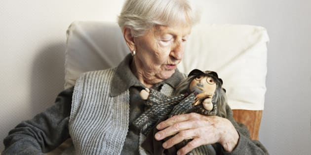 porttrait of a 90 years old woman, with her handmade doll