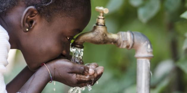 Young African girl drinking clean water from a tap. Hands cupped of an African child with water pouring from a tap in the streets of the African city Bamako, Mali.