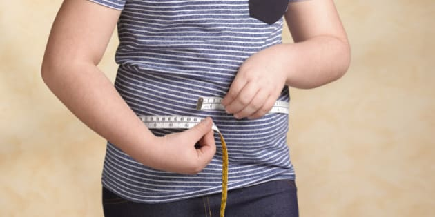 Obese child measuring herself