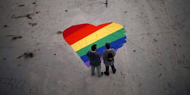 Fer Franco, 25, (L) and his partner Rafa Varon, 23, stand next to a heart-shaped cloth with rainbow colors as they pose for a photo, to mark Gay Pride day, in downtown Malaga, southern Spain, June 28, 2015. The heart-shaped cloth with rainbow colors is the logo of the Andalusian Federation of Lesbian, Gay, Bisexual, Transgender and Intersex (LGBTI) Arco Iris, which Franco and Varon are volunteers of.  REUTERS/Jon Nazca