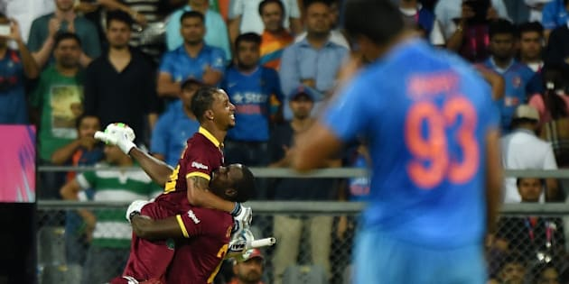 West Indies Lendl Simmons(L)celebrates after winning the World T20 cricket tournament semi-final match against India at The Wankhede Cricket Stadium in Mumbai on March 31, 2016. / AFP / PUNIT PARANJPE        (Photo credit should read PUNIT PARANJPE/AFP/Getty Images)