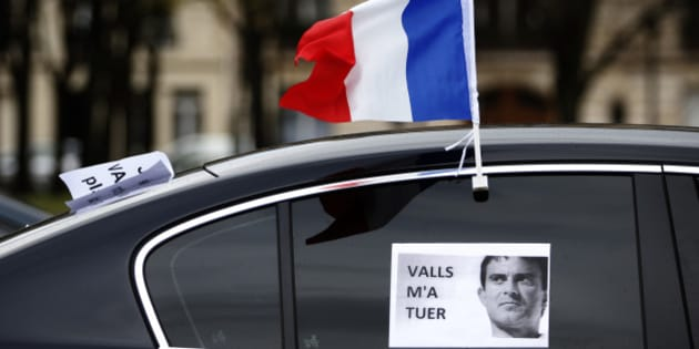 """A French flag flies from a car during a demonstration by LOTI transport drivers (public transport on demand) and VTC drivers, including Uber France, to denounce the measures in favor to French taxis drivers in Paris, France, February 3, 2016. The placard """"Valls killed me"""".   REUTERS/Charles Platiau TPX IMAGES OF THE DAY"""