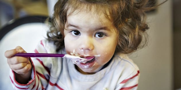 Young girl (18 months) eating yoghurt