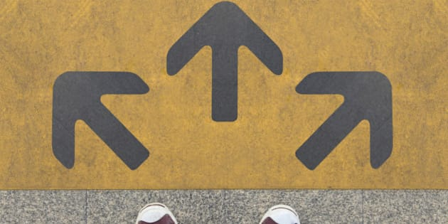 Pair of shoes standing on a road with three grey arrow on the yellow background
