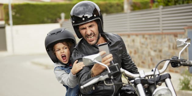 Father and son making faces while taking self portrait through mobile phone on motorbike