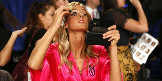Model Erin Heatherton from the U.S. applies eye makeup backstage before the 2011 Victoria's Secret Fashion Show in New York November 9, 2011.    REUTERS/Mike Segar (UNITED STATES - Tags: FASHION)