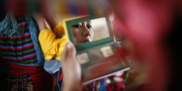 "A Tibetan girl in traditional attire looks into the mirror as she prepares ahead of a performance during a function organised to mark ""Losar"" or the Tibetan New Year in Kathmandu, Nepal, February 11, 2016. REUTERS/Navesh Chitrakar"