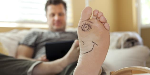 Mans foot with half a face drawn on it using a digital tablet.