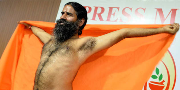 Indian Yoga guru Baba Ramdev stretches after addressing a press conference in Bangalore on March 18, 2016, ahead of a five day yoga camp. / AFP / Manjunath Kiran        (Photo credit should read MANJUNATH KIRAN/AFP/Getty Images)