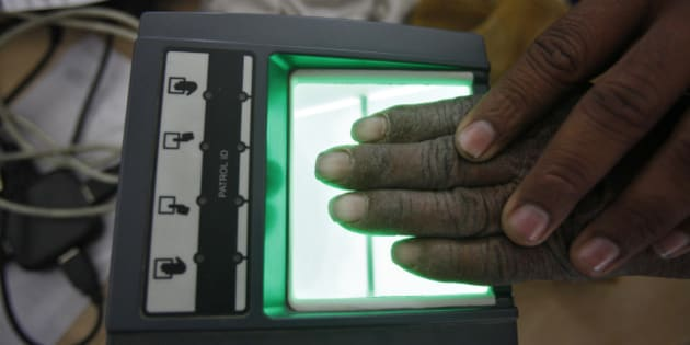 A villager goes through the process of a fingerprint scanner for the Unique Identification (UID) database system at an enrolment centre at Merta district in the desert Indian state of Rajasthan February 22, 2013. In a more ambitious version of programmes that have slashed poverty in Brazil and Mexico, the Indian government has begun to use the UID database, known as Aadhaar, to make direct cash transfers to the poor, in an attempt to cut out frauds who siphon billions of dollars from welfare schemes. Picture taken February 22, 2013. REUTERS/Mansi Thapliyal (INDIA - Tags: BUSINESS SOCIETY POVERTY SCIENCE TECHNOLOGY)