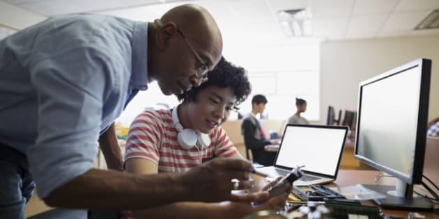 High school teacher and student assembling computer