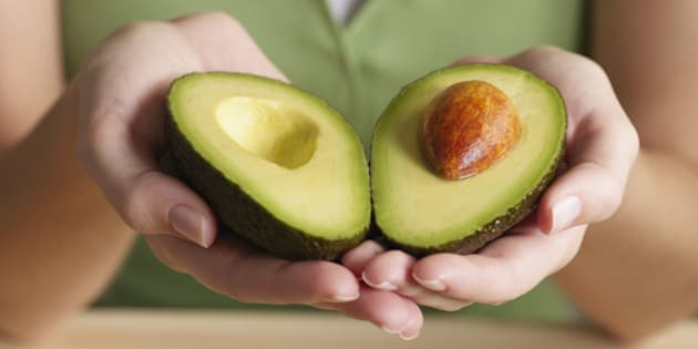 Woman holding halved avocado