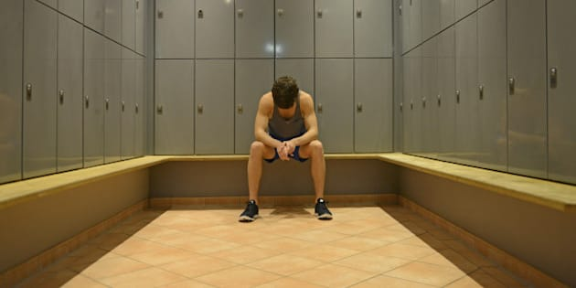 Teenage boy in gym locker room, looking down