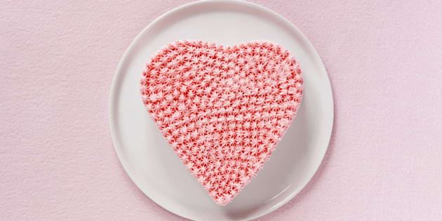 Pink heart shaped cake decorated whipped cream,aerial view.