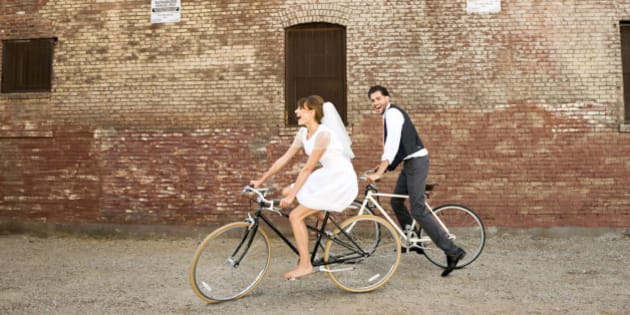 Bride and Groom riding their bikes, horizontal, brick wall