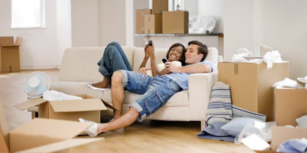 A young couple relaxing on a sofa and texting after moving into a house.