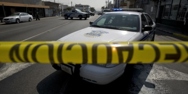 Police vehicles guard the site where a woman was found dead inside a car, two blocks away from a police station in Tijuana, Mexico, Thursday, May 14, 2009. (AP Photo/Guillermo Arias)