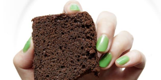 Green nail hand holding bitten chocolate cake.
