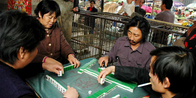 With little work to do without chickens, vendors play the popular Chinese game of mahjong next to empty cages meant for live fowl lined up at their poultry stalls at a Beijing market Friday, Nov. 4, 2005. China reported its fourth bird flu outbreak in three weeks, saying the virus killed 8,940 chickens in a village in the country's northeast and prompted authorities to destroy 369,900 other birds. The outbreak occurred Oct. 26 in Badaohao, a village in Liaoning province, east of Beijing, the Agriculture Ministry said in a report posted late Thursday on the Web site of the Paris-based World Organization for Animal Health. (AP Photo)