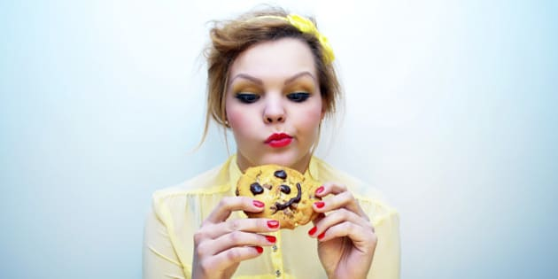 Young woman with ginger hair wearing a yellow blouse and colourful make-up staring at a smiling chocolate chip cookie.