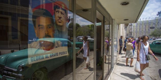 Reflected on a window with a poster of Venezuela's President Nicolas Maduro and late President Hugo Chevez people walk on Neptuno Street in Havana, Cuba, Friday, March 18, 2016. Venezuela's President Maduro flew to Cuba on Friday for a day of high-level meetings and ceremonies that appeared designed to send a message of socialist solidarity two days before Barack Obama becomes the first U.S. president to visit the island in nearly 90 years. (AP Photo/Desmond Boylan)