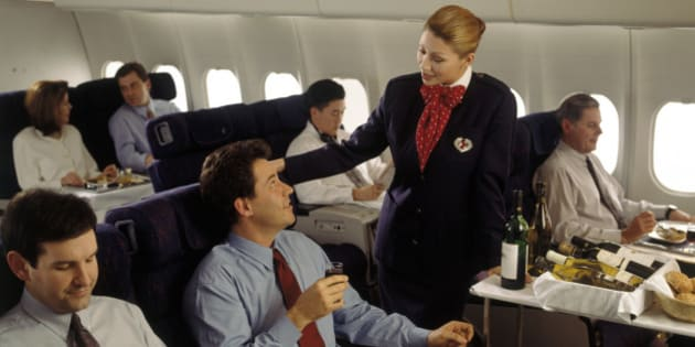 Executive enjoying in-flight meal with wine