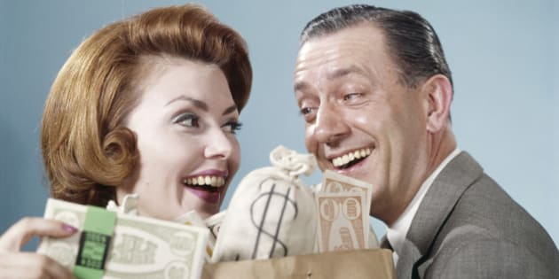 1960s HAPPY COUPLE MAN WOMAN HOLDING SHOPPING BAG FULL OF MONEY LAUGHING LOOKING AT EACH OTHER  (Photo by H. Armstrong Roberts/ClassicStock/Getty Images)