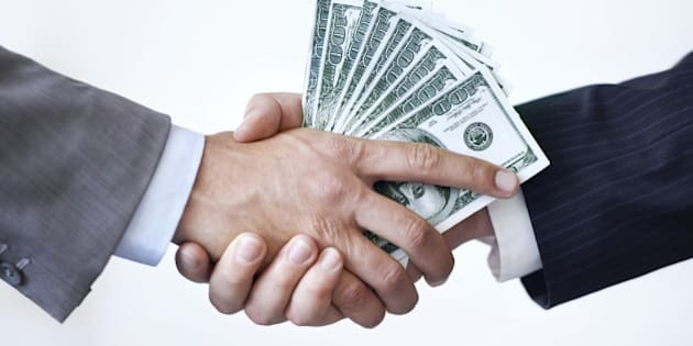 Studio shot of two men shaking hands after making a monetary deal