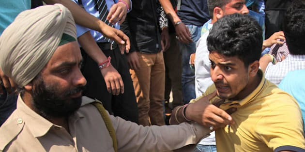 A policeman detains a student during a protest against police action on students of National Institute of Technology (NIT) in Srinagar while they were protesting against students of Kashmiri origin celebrating India's loss to West Indies in the semifinal of the ICC T20 World Cup cricket, in Jammu, India, Thursday, April 7, 2016. (AP Photo/Channi Anand)