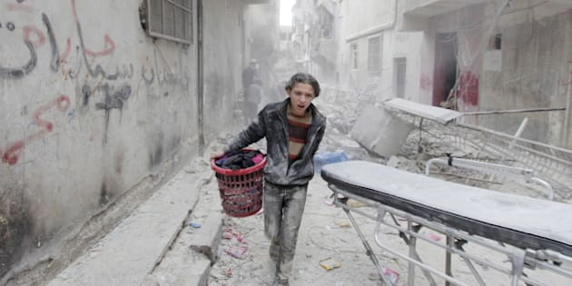 A boy carries his belongings at a site hit by what activists said was a barrel bomb dropped by forces loyal to Syria's President Bashar al-Assad in Aleppo's al-Fardous district April 2, 2015. REUTERS/Rami Zayat      TPX IMAGES OF THE DAY