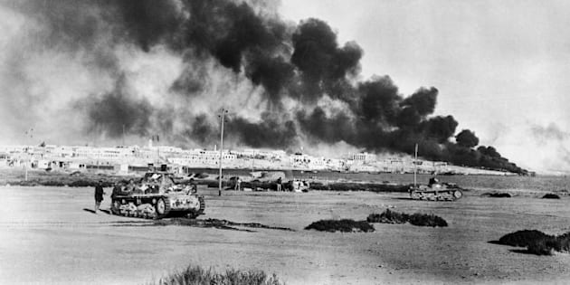 Tobruk, strategic Libyan port abandoned by the Nazis, was reoccupied by the British, Nov. 13, 1942. This photo shows Tobruk harbor and the city beyond, with fires burning, when it was previously captured by British forces early in 1941. British tanks wait in foreground. (AP Photo)