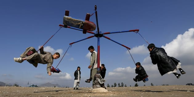 Afghan boys play on a merry-go-round during celebrations for the Afghan New Year, known as Newroz in Kabul, Afghanistan March 20, 2016. REUTERS/Mohammad Ismail