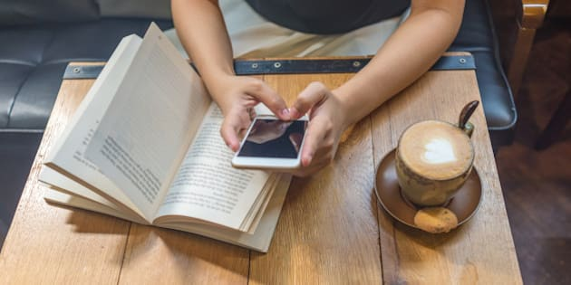 Playing game on smartphone or reading paper book