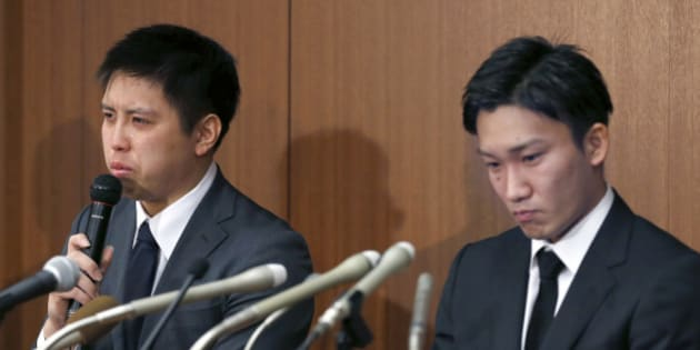 Japanese badminton player Kenichi Tago, left, speaks with his teammate Kento Momota as they apologize for gambling at an illegal casino during a press conference in Tokyo, Friday, April 8, 2016. The two were admitted to gambling at an illegal casino, damaging their chances of competing at the Olympics in Rio de Janeiro. (AP Photo/Shizuo Kambayashi)