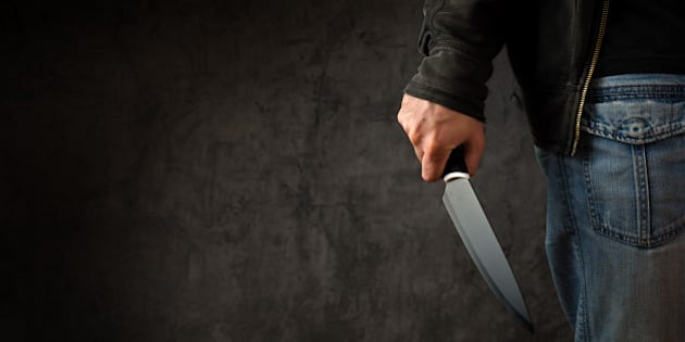 Evil criminal with large sharp knife ready for robbery or to commit a homicide