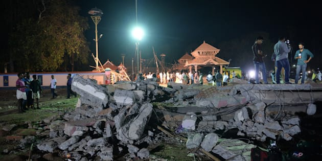 Onlookers and medias stand amidst the debris in the aftermath of the deadly fire explosion that rocked the Hindu Goddess, Puttingal Devi Temple in Paravur, 60kms North-West of Thiruvananthapuram in Kerala on the late evening of April 10, 2016.  More than 100 people have died and 350 injured when fireworks meant to be lit for festivities caught fire and exploded near the temple where thousands of people had gathered to witness the extravanganza on the early hours of April 10. / AFP / MANJUNATH KIRAN        (Photo credit should read MANJUNATH KIRAN/AFP/Getty Images)