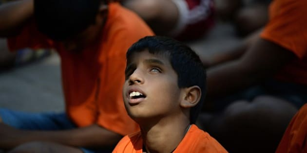 A visually impaired Indian child looks upwards as a ray of sunlight falls on his face while waiting to beak a dahi-handi (curd-pot) suspended in the air during a celebration for Janmashtami at the Victoria School for the Blind in Mumbai on September 5, 2015. The Hindu festival of 'Janmashtami', marks the birth of the Hindu god Lord Krishna. AFP PHOTO/ Indranil MUKHERJEE        (Photo credit should read INDRANIL MUKHERJEE/AFP/Getty Images)