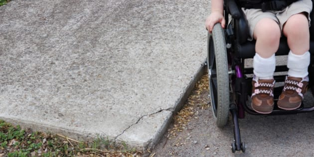 Young caucasion female child that is wheelchair bound with braces on her ankles that is trying to use a sidewalk that is not accessable to her chair.