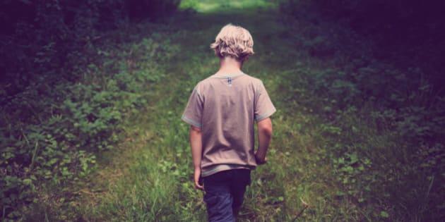 7 year old boy walks down path through woods