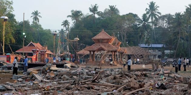 Indian bystanders gather among debris and building wreckage of The Puttingal Devi Temple in Paravur some 60kms north-west of Thiruvananthapuram on April 11, 2016. 