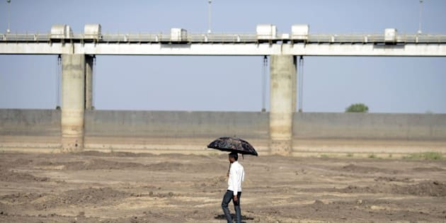 An Indian man holds an umbrella as he walks on the dry reservoir bed next to Gunda Dam by Gunda village in Botad district, some 150 km from Ahmedabad in India's western Gujarat state, on April 1, 2016. 