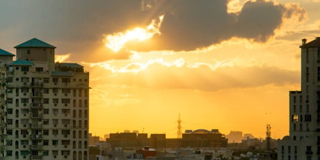 Gurgaon apartments at sunset with light rays passing through the clouds and giving a golden glow