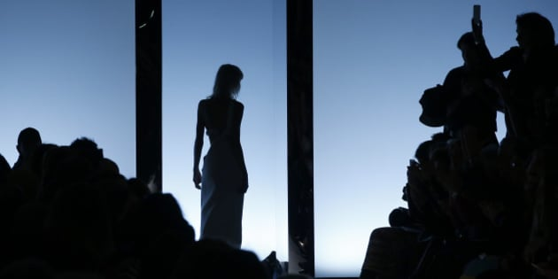 A model is silhouetted as she wears a creation for Fausto Puglisi women's Fall-Winter 2016-2017 collection, part of the Milan Fashion Week, unveiled in Milan, Italy, Wednesday, Feb. 24, 2016. (AP Photo/Antonio Calanni)