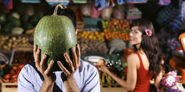 Man Stands by a Market Stall Holding a Watermelon in Front of His Face